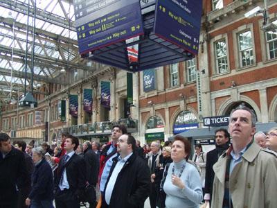 ヴィクトリア駅:プラットフォーム番号を見上げる通勤者